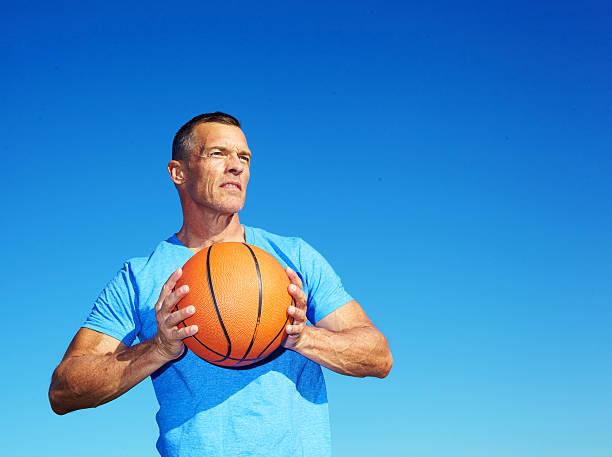 Man Holding Basketball Against Clear Blue Sky stock photo