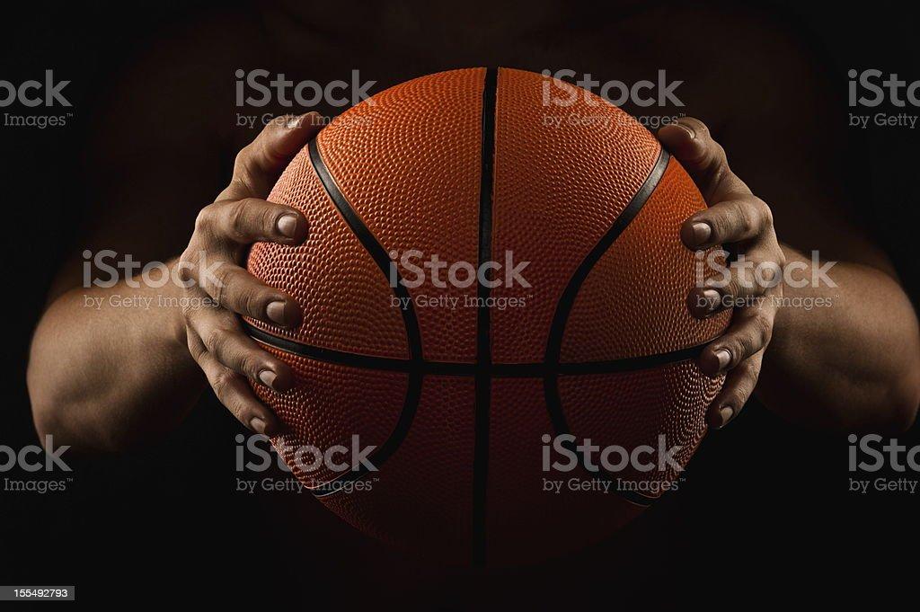Man holding basketball in the dark stock photo