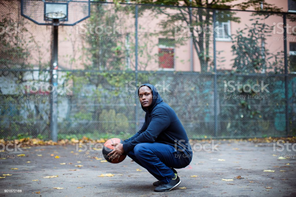 Man holding basketball while crouching by fence royalty-free stock photo