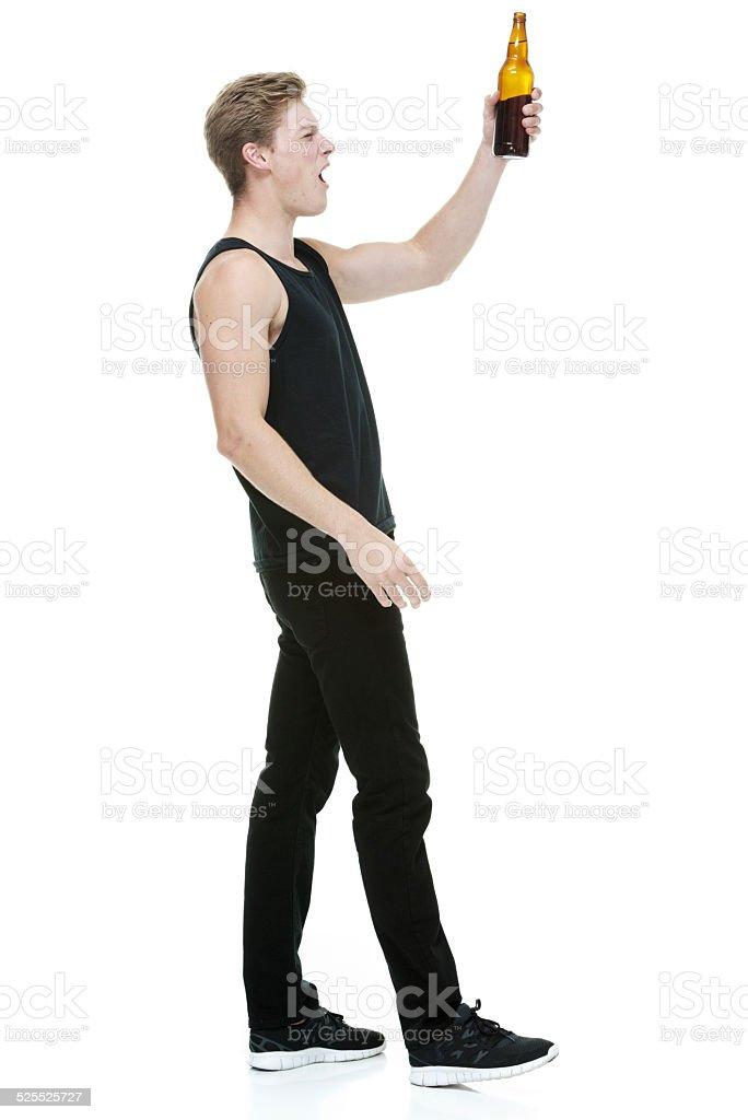 Hombre que agarra botella de cerveza & aclamando - foto de stock