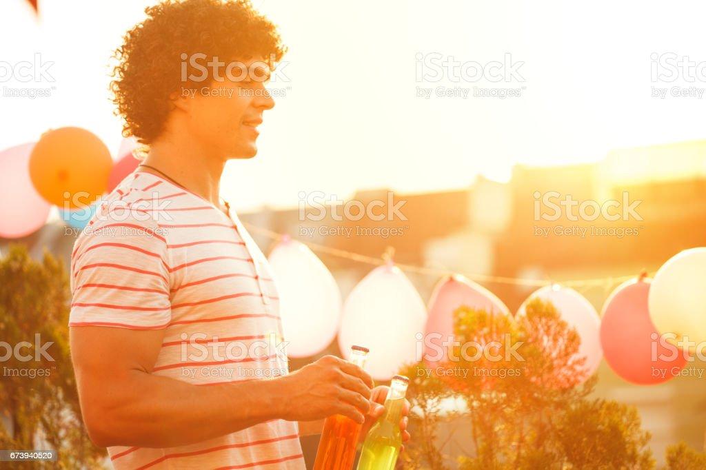 Man holding beer bottles on rooftop foto de stock royalty-free