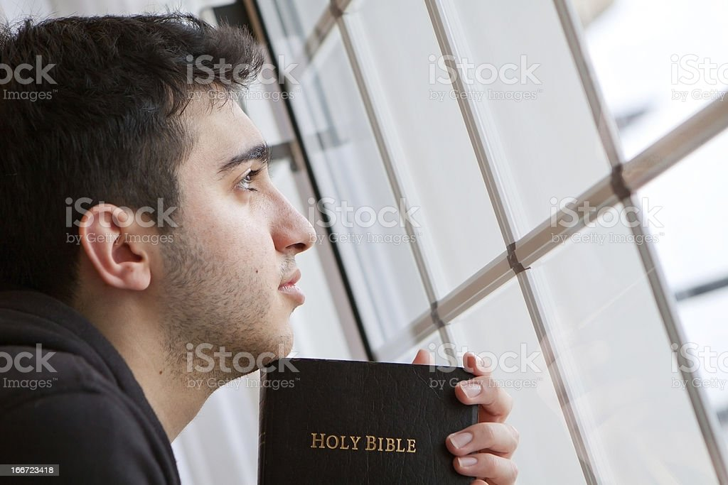 Man Holding Bible Looking Out Window royalty-free stock photo
