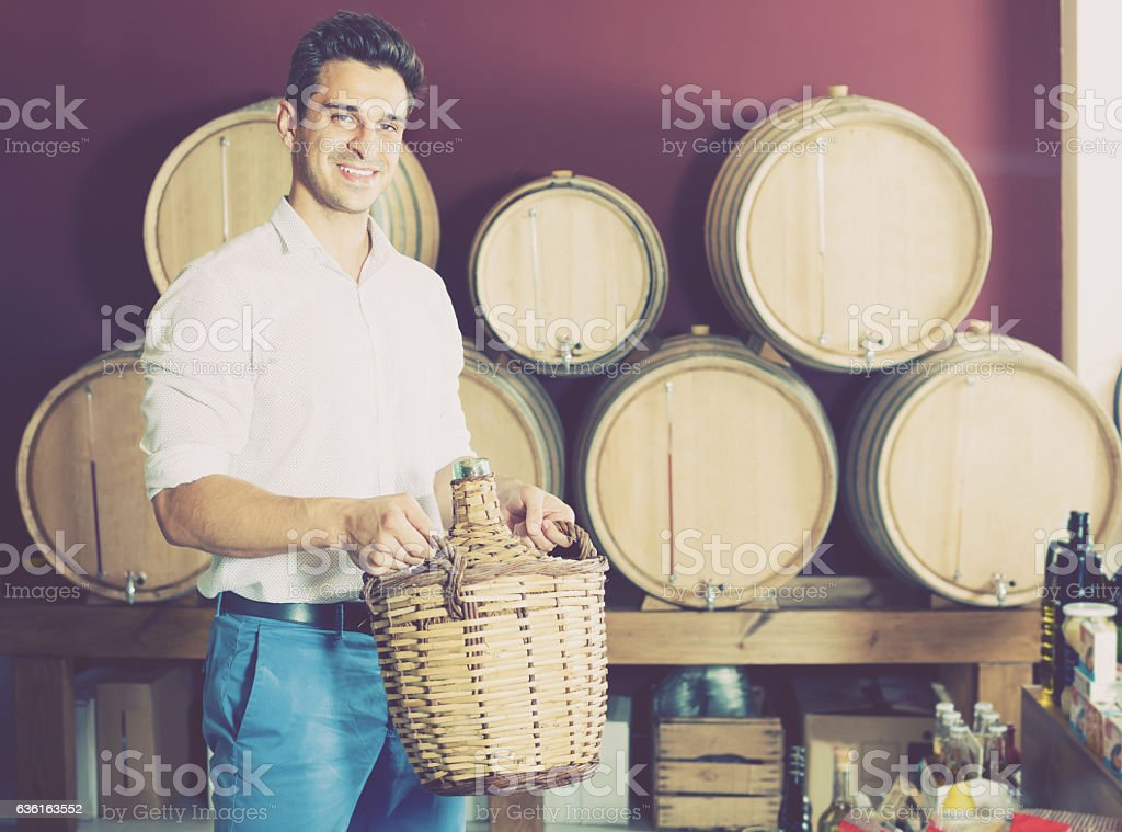 man holding big wicker bottle with wine stock photo