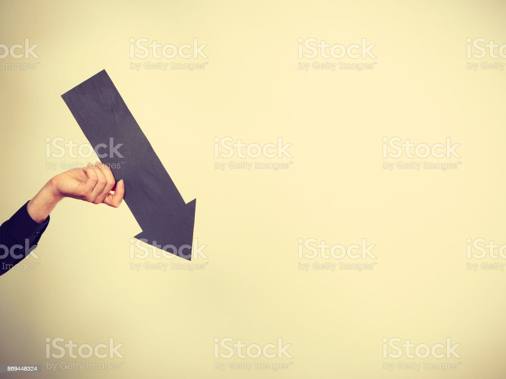 Man holding black arrow pointing right stock photo