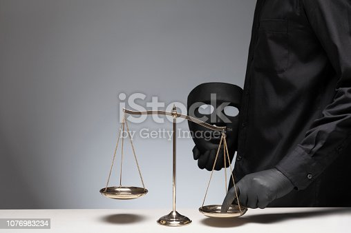 824305956 istock photo Man holding black evil mask in one hand pressing the scale on the gray background 1076983234