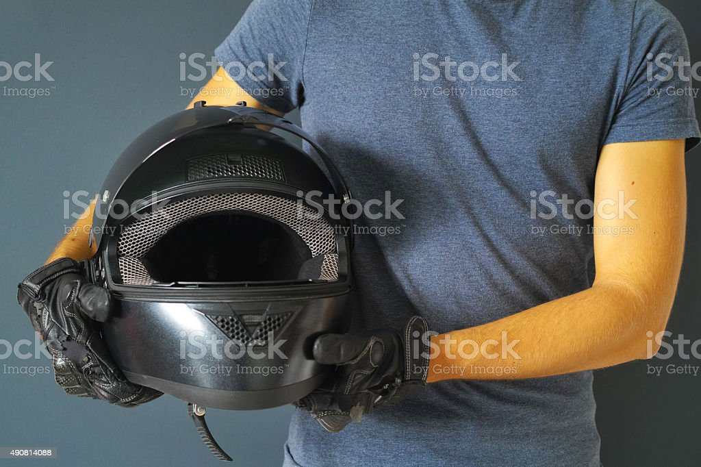 Man Holding Black Motorcycle Helmet With Hand In Gloves stock photo