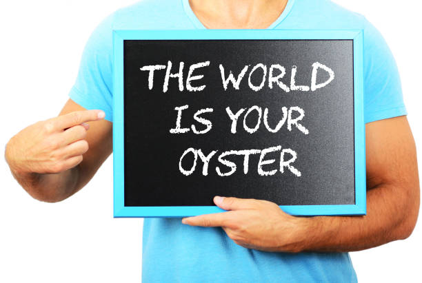 Man holding blackboard in hands and pointing the word THE WORLD IS YOUR OYSTER stock photo