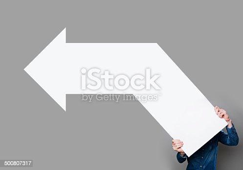 istock Man holding blank arrow sign 500807317