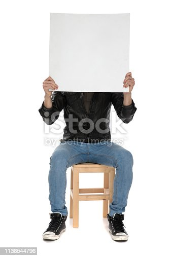 istock man holding blank billboard on hand while covering his face 1136544796