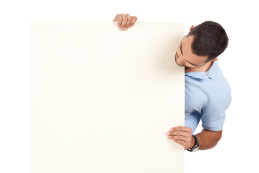 Man in blue polo shirt holding the right corner of blank billboard. Isolated image on white background.