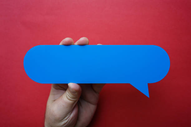 Man holding blank blue speech bubble on red background. stock photo