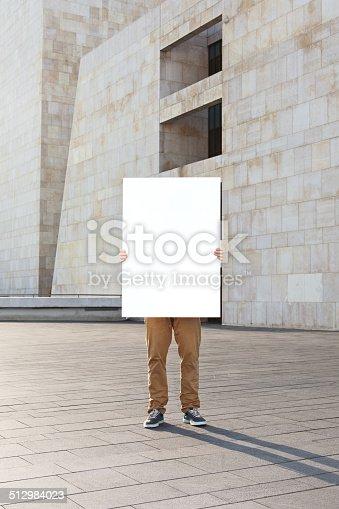 istock man holding blank poster 512984023