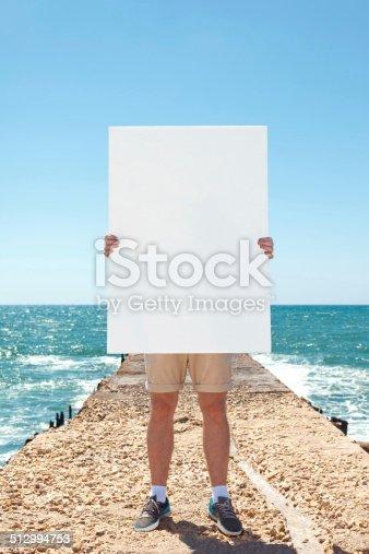 istock man holding blank poster 512994753