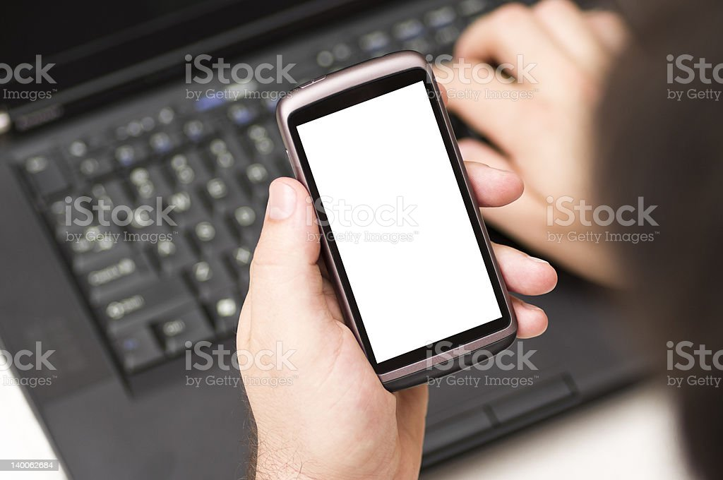 Man holding blank Smartphone while using a laptop royalty-free stock photo