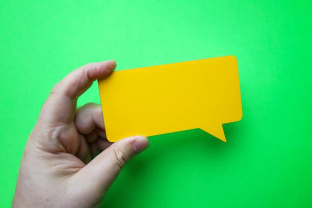 Man holding blank yellow speech bubble on green background. stock photo