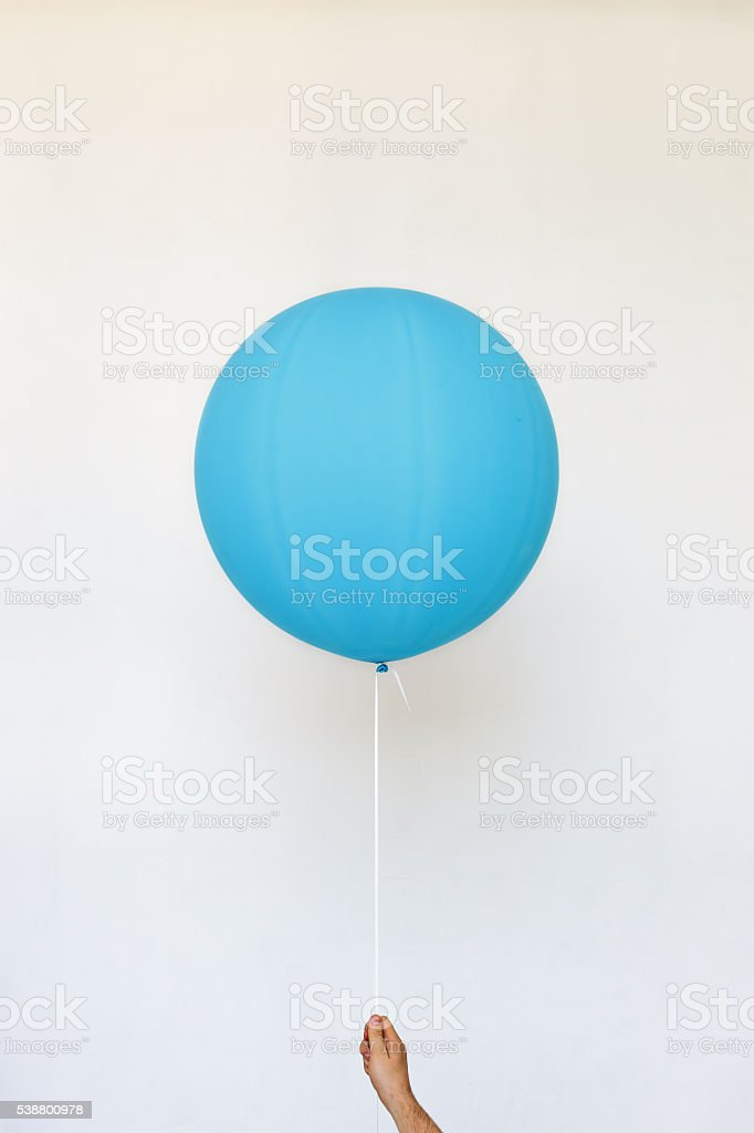 Man holding blue balloon on a white background. stock photo