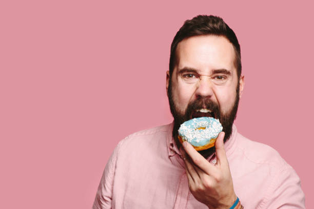 Man holding blue donut and taking a big bite A man with beard looking at camera about to take a big bite of a blue donut he is holding in his hand greed stock pictures, royalty-free photos & images