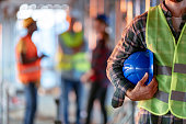 Man holding blue helmet close up. Construction man worker with office and people in background. Close up of a construction worker's hand holding working helmet.