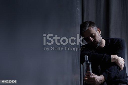 istock Man holding bottle of alcohol 640220806