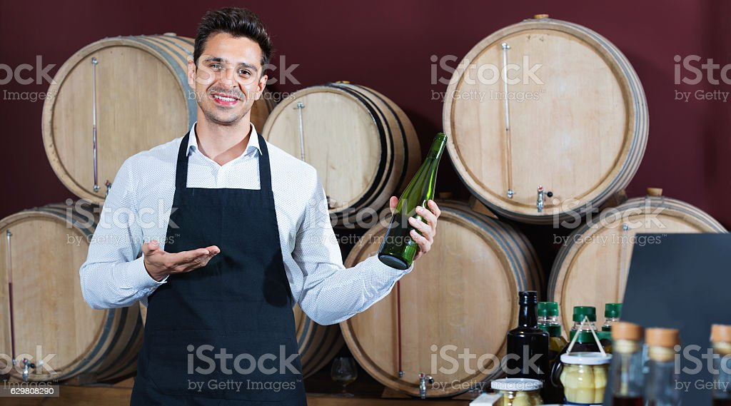 Man  holding bottle of wine and standing in alcohol section stock photo