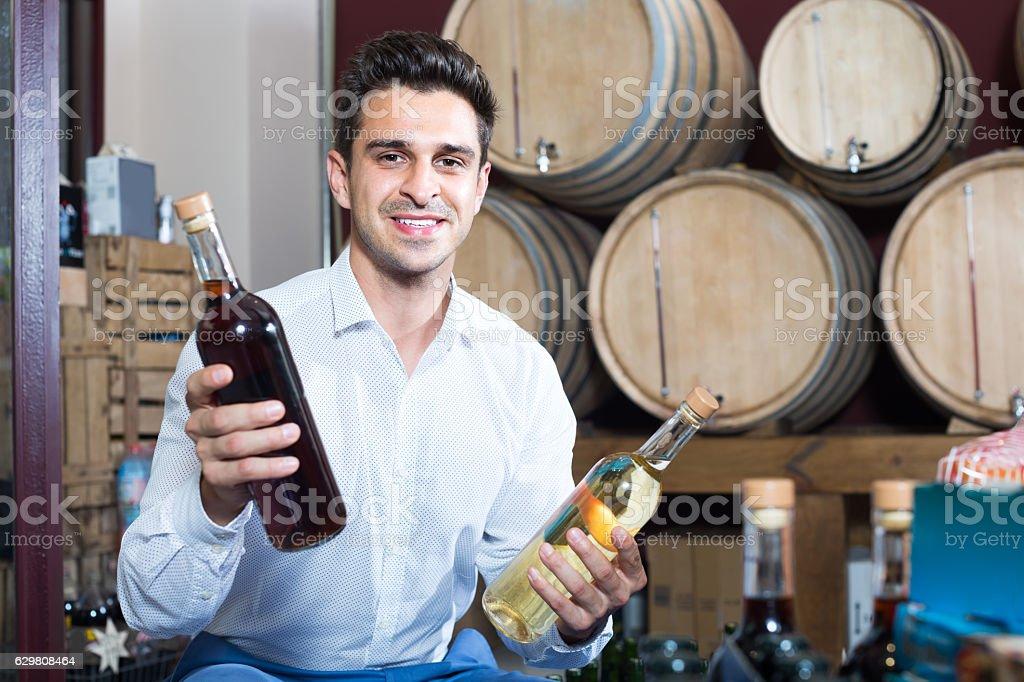 man holding bottle of wine in cellar stock photo