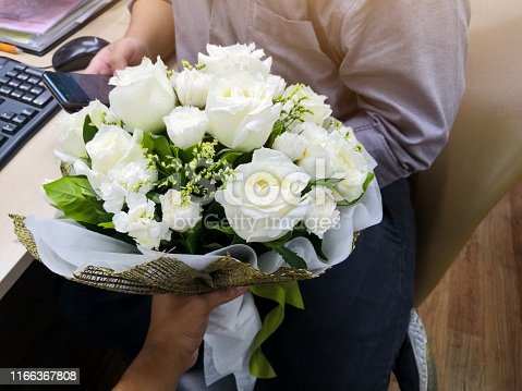 man holding bouquet of white roses at office. boyfriend surprise boyfriend with flower in valentine's day. celebrate anniversary, love & relationship concept.