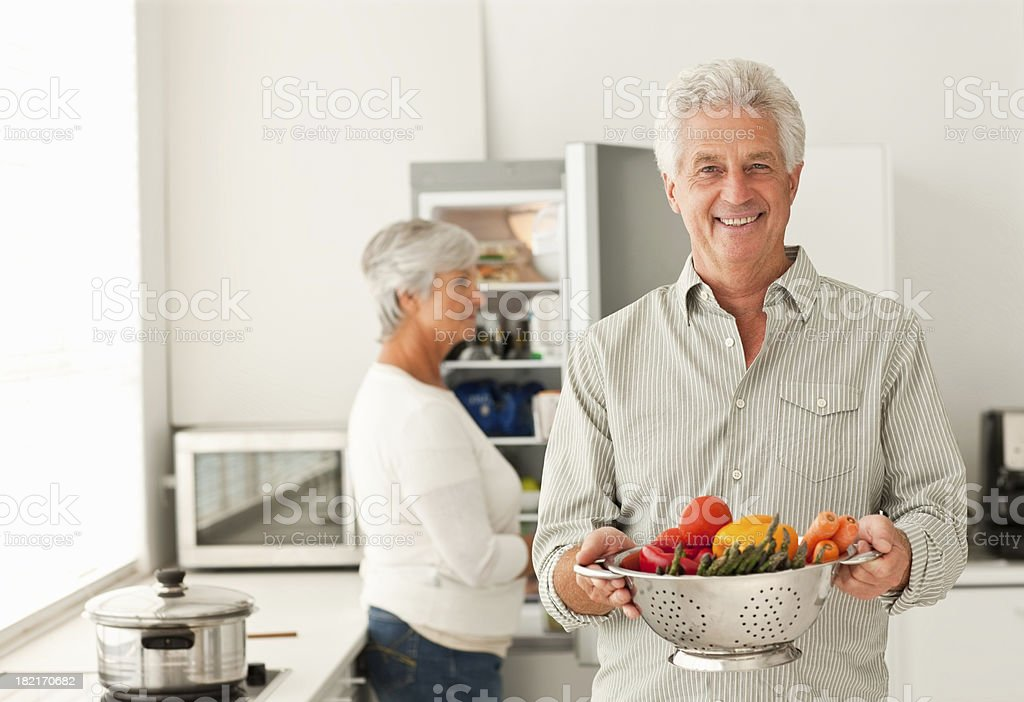 Man holding bowl of vegetables with wife at the back royalty-free stock photo