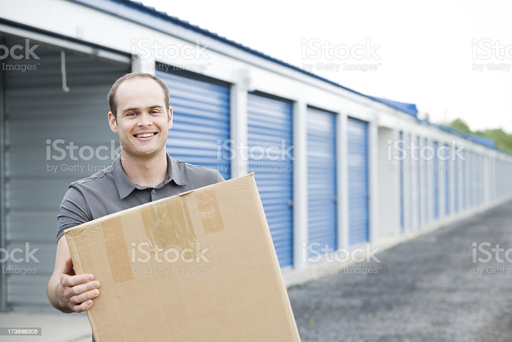 Man Holding Box Outside Self Storage Unit stock photo