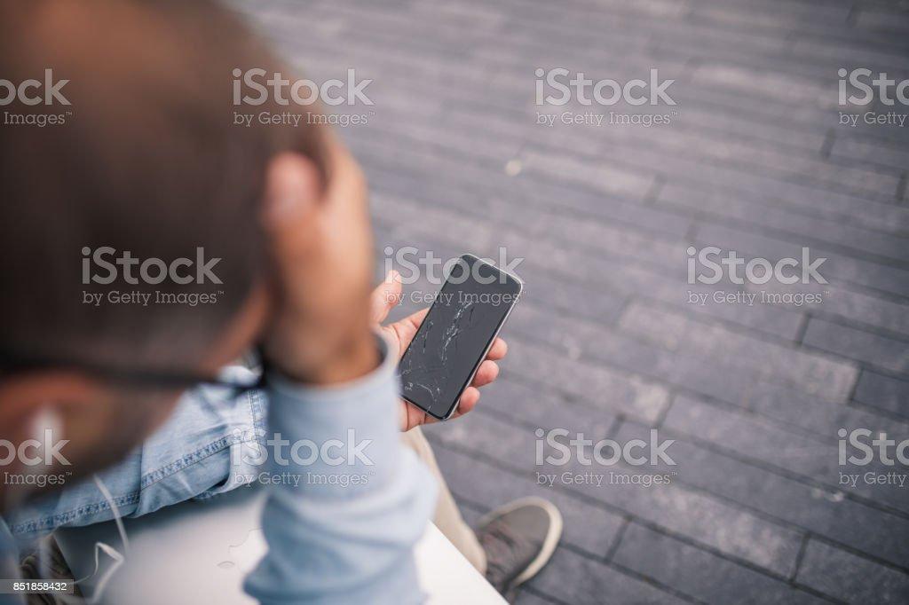 Man holding broken  phone stock photo