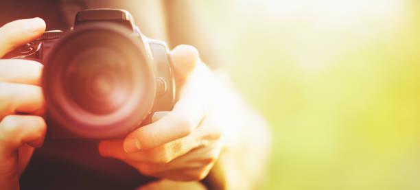 man holding camera close-up - spiegelreflexcamera stockfoto's en -beelden