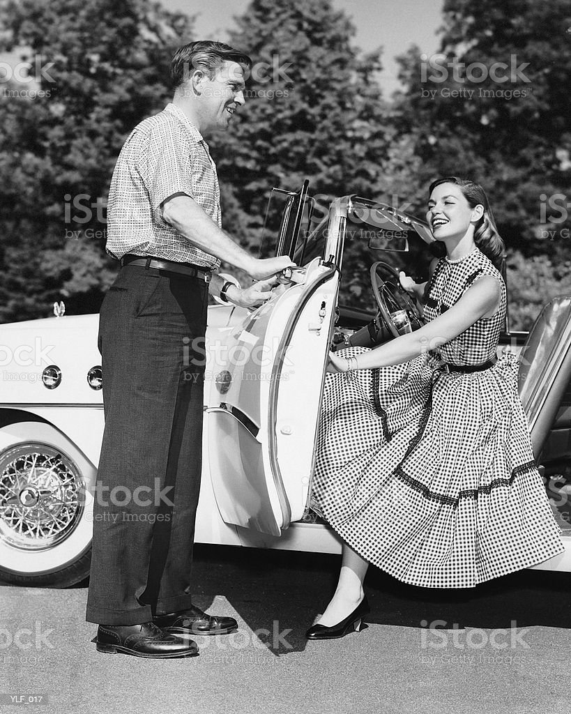 Man holding car door open for woman royalty free stockfoto