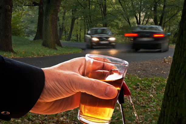 Man Holding Car Key and Glass of Spirits stock photo