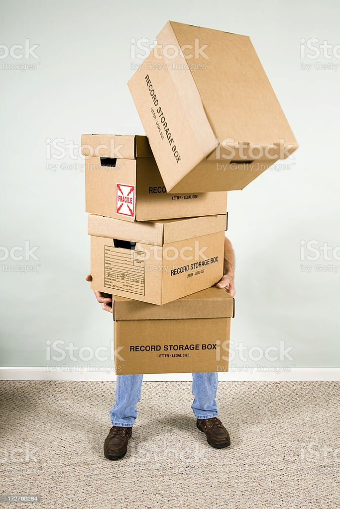 Man holding, carrying many cardboard boxes. Falling from stack. royalty-free stock photo
