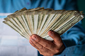 istock A Man Holding Cash To Pay Bills and Payments 1171982800