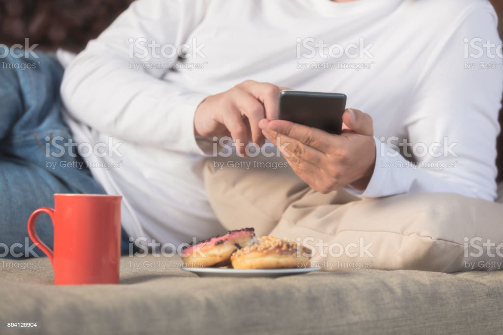 Man holding cellphone, coffe mug with donuts on the sofa. royalty-free stock photo
