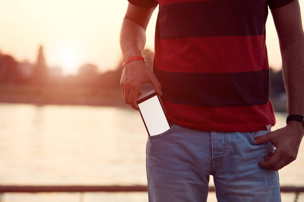 Man holding cellphone in pocket near river. stock photo