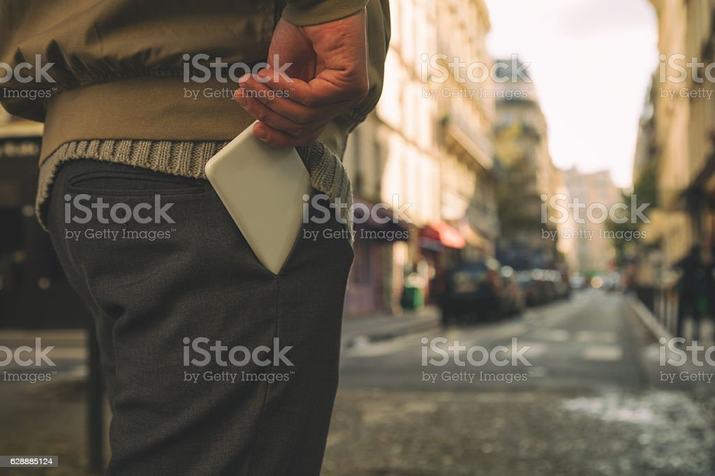 Man holding cellphone in pocket. stock photo