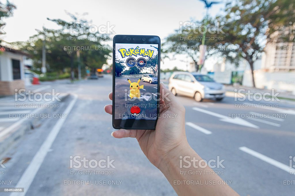Man holding cellphone playing Pokemon Go. stock photo