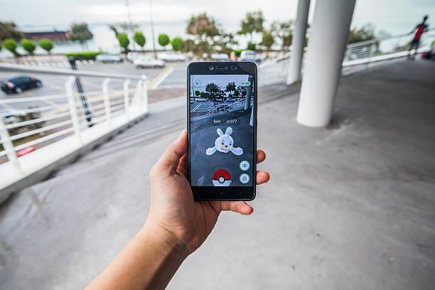 man holding cellphone playing pokemon go. - pflanzen pokemon stock-fotos und bilder
