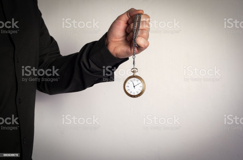 Man holding chain clock on white background stock photo
