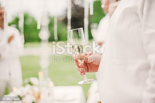 Man Holding Champagne Glass At A Summer Party Stock Photo & More Pictures of 2015