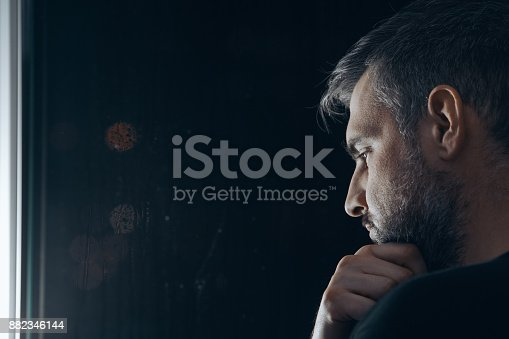 istock Man holding chin beside window 882346144