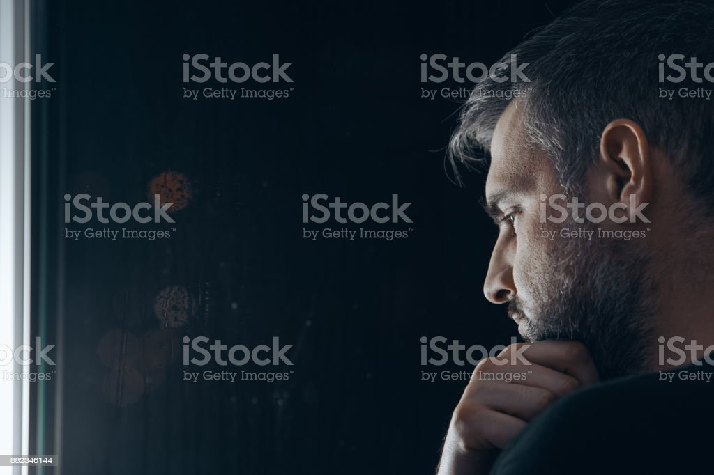 Man holding chin beside window stock photo
