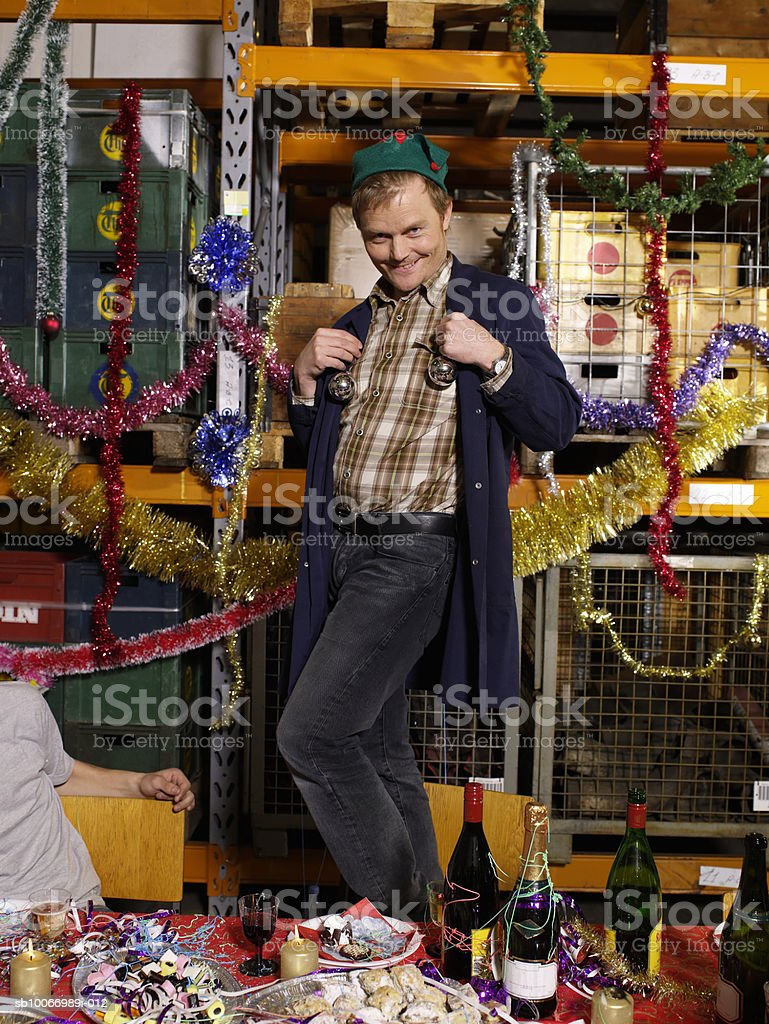Man holding christmas baubles against chest standing on casitas table in warehouse, portrait royalty-free stock photo