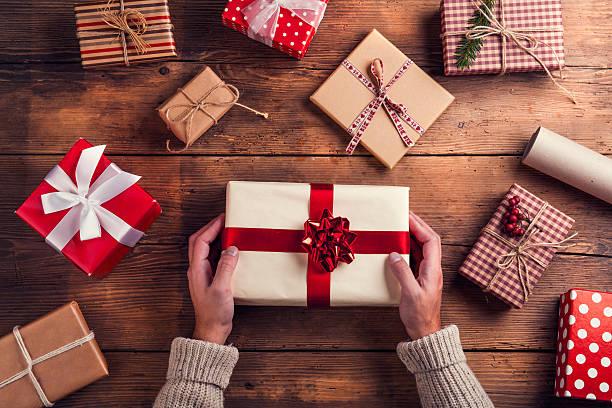 mann hält weihnachtsgeschenk - weihnachtsideen stock-fotos und bilder