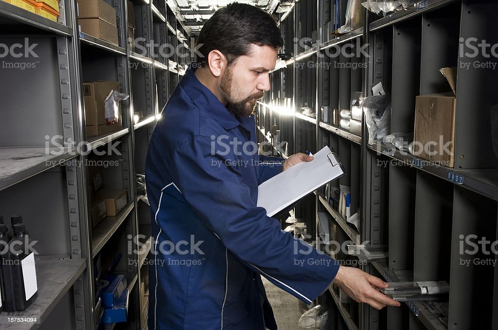 Man Holding Clipboard in Industrial Warehouse royalty-free stock photo