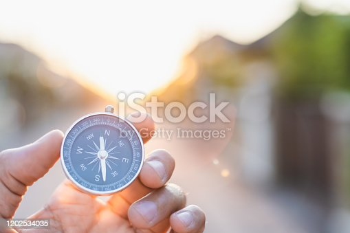 istock man holding compass on blurred background. for activity lifestyle outdoors freedom or travel tourism and inspiration backpacker alone tourist travel or navigator image. 1202534035