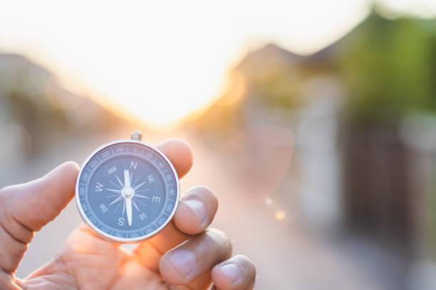 mann hält kompass auf verschwommenen hintergrund. für aktivität lifestyle outdoors freedom oder reise-tourismus und inspiration backpacker allein touristenreisen oder navigator bild. - karte navigationsinstrument stock-fotos und bilder
