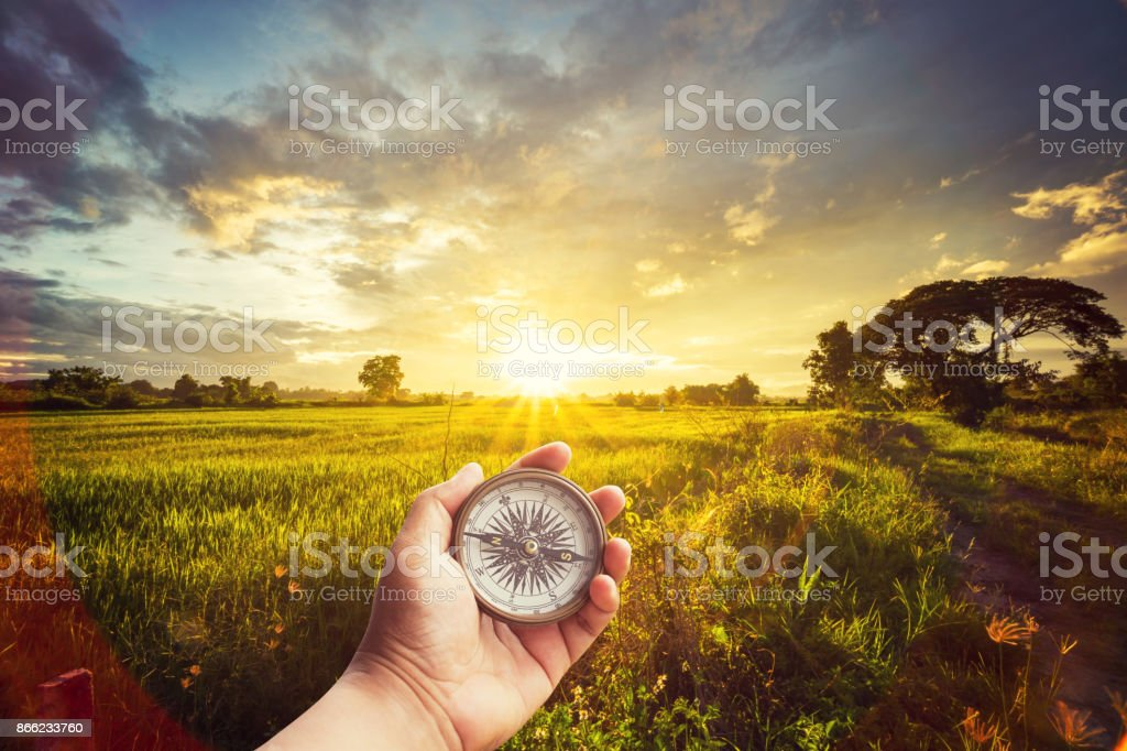A man holding compass on hand at field and sunset for navigation guide. stock photo