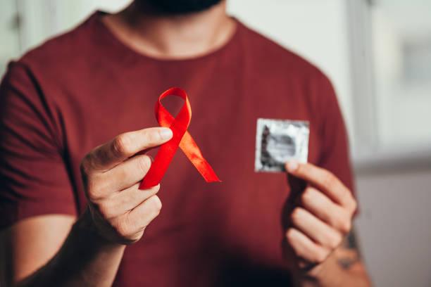 mann hält kondom und rotes band für hiv-krankheit bewusstsein, 1. dezember welt-aids-tag konzept. - aids stock-fotos und bilder